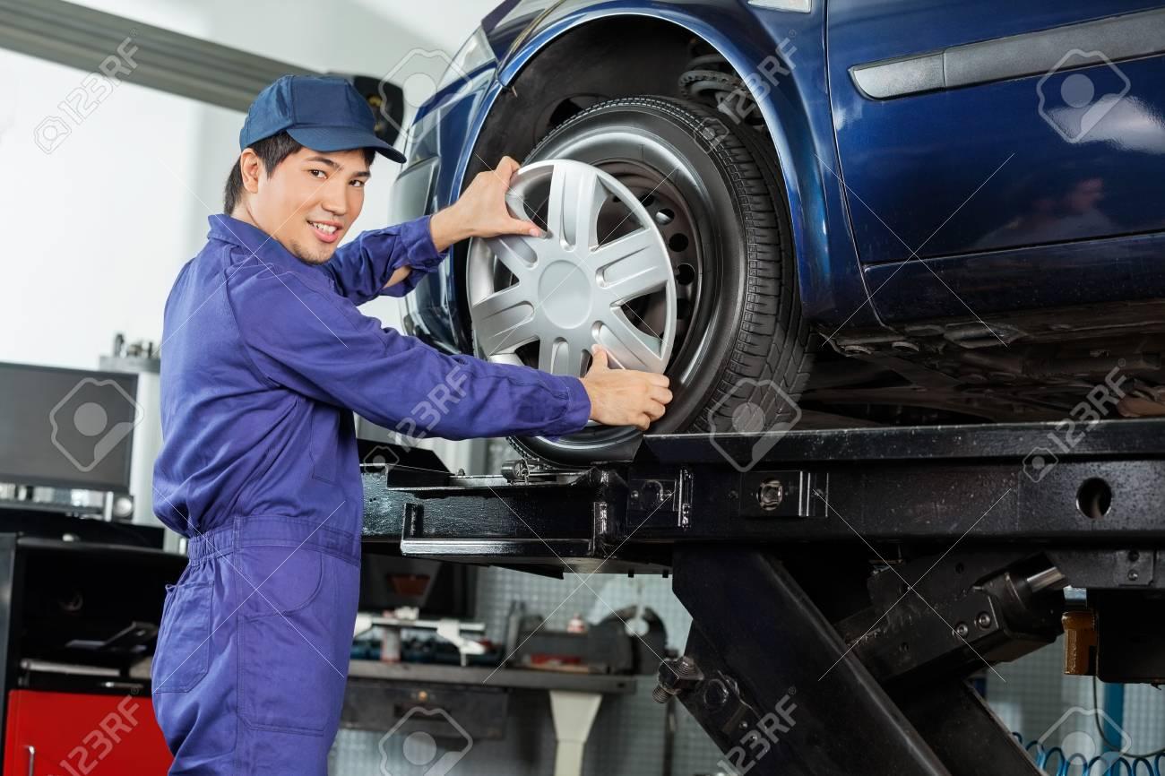 56707223-vue-de-côté-portrait-de-mécanicien-confiant-fixation-enjoliveur-au-pneu-de-voiture-au-garage.jpg